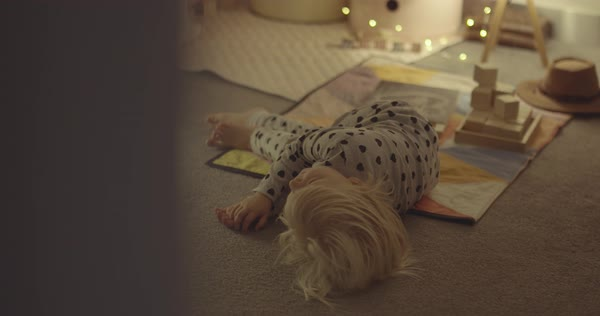 Hand-held shot of a little girl in pajamas rolling on floor Royalty-free stock video