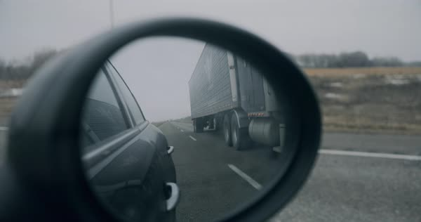 Point-of-view shot of a truck seen through the rearview mirror of the car Royalty-free stock video