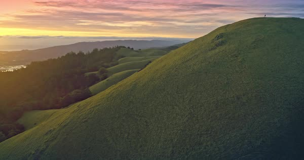 Aerial of grass hills on a mountain ridge at sunset flying over people Royalty-free stock video