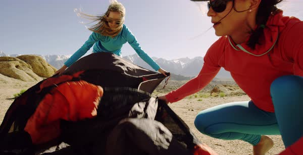 Hand-held shot of two women spreading out a tent in blowing wind Royalty-free stock video
