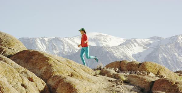 Tracking shot of a female hiker running and jumping on rocks Royalty-free stock video