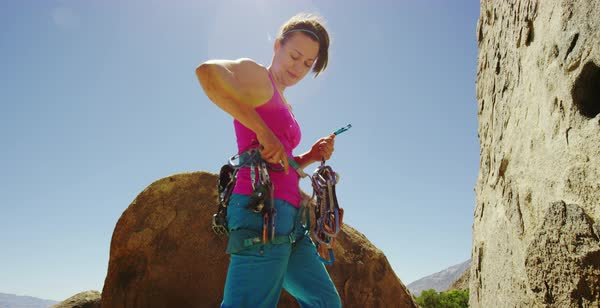 Hand-held shot of a female rock climber putting climbing cams on her harness Royalty-free stock video