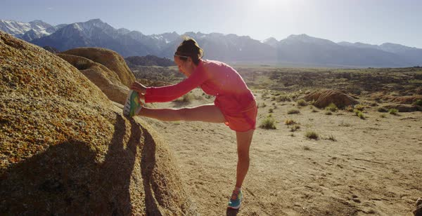 Slow motion shot of a female runner stretching her legs in Alabama Hills Royalty-free stock video