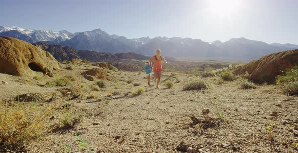 Slow motion shot of two women running past camera in Alabama Hills Royalty-free stock video