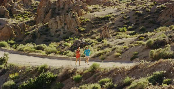 Tracking shot of two women running on a dirt road in a rocky desert Royalty-free stock video