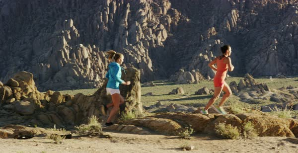 Slow motion shot of two women running among rock formations in Alabama Hills Royalty-free stock video