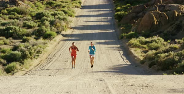Tilt-down shot of two women running on a dirt road in Alabama Hills Royalty-free stock video