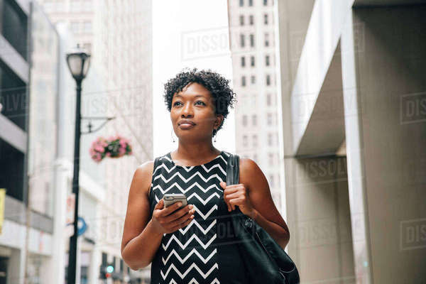 Pensive businesswoman standing in city holding cell phone Royalty-free stock photo