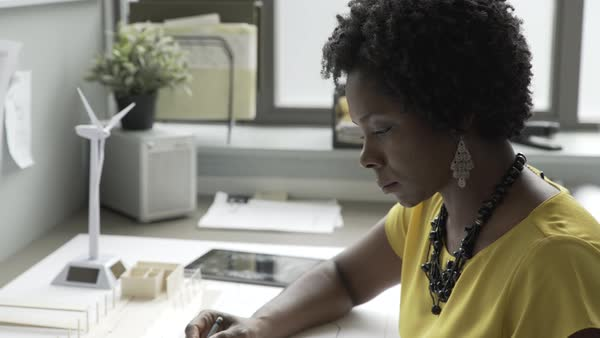 Hand-held shot of a woman working on renewable energy project with concept models on her desk Royalty-free stock video