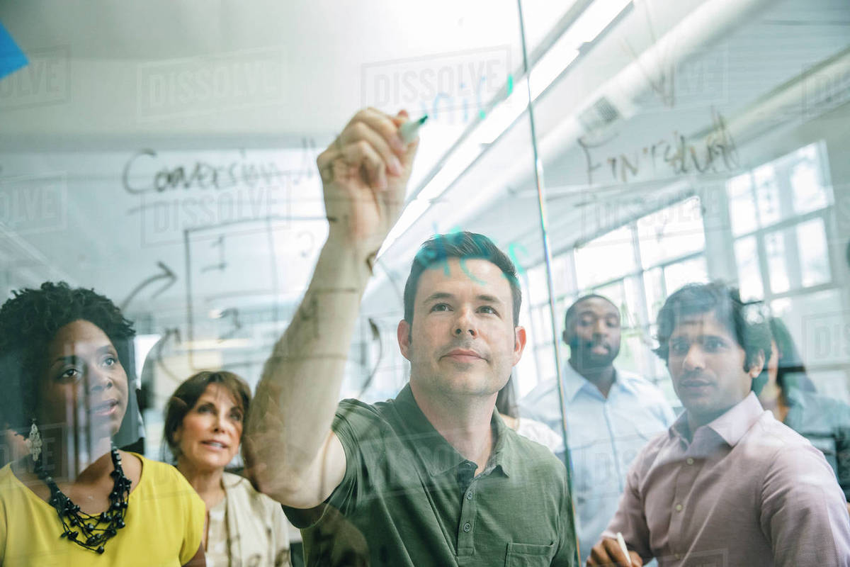 Man writing on a glass wall during an office meeting Royalty-free stock photo