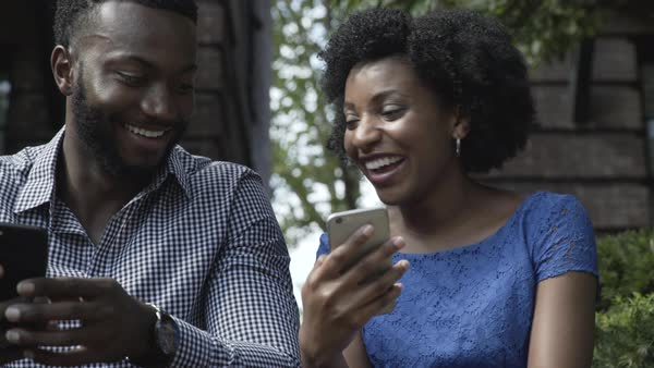 Gimbal shot of a young couple looking at a smartphone outdoors Royalty-free stock video