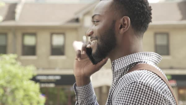 Tracking shot of a man talking on a cell phone outdoors Royalty-free stock video