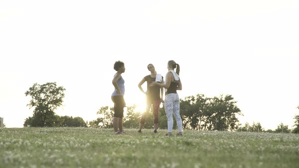Dolly shot of three women standing in sportswear and talking in a park after working out Royalty-free stock video
