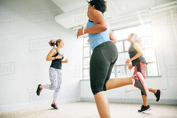 Instructor and students running in place in studio Royalty-free stock photo