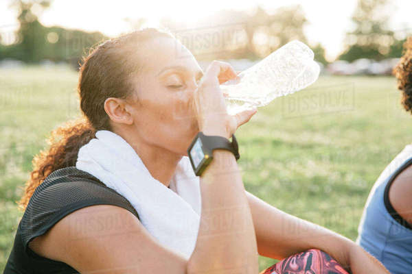 Woman sitting in field drinking water Royalty-free stock photo