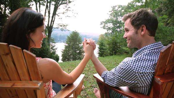 Couple holding hands in lawn chairs in backyard Royalty-free stock video