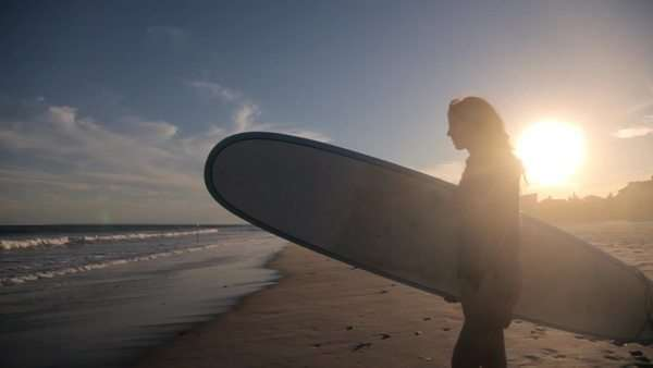 Silhouette of surfer carrying surfboard to ocean Royalty-free stock video