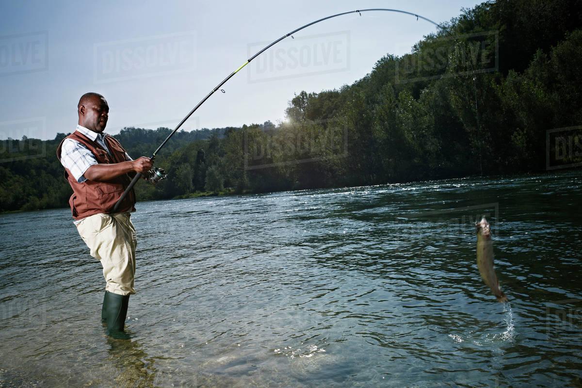 Black Man Catching Fish In Stream Stock Photo Dissolve