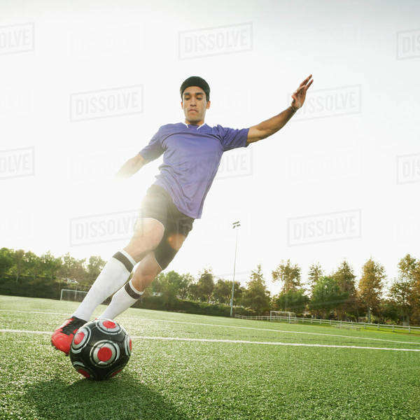 Mixed race soccer player kicking soccer ball Royalty-free stock photo