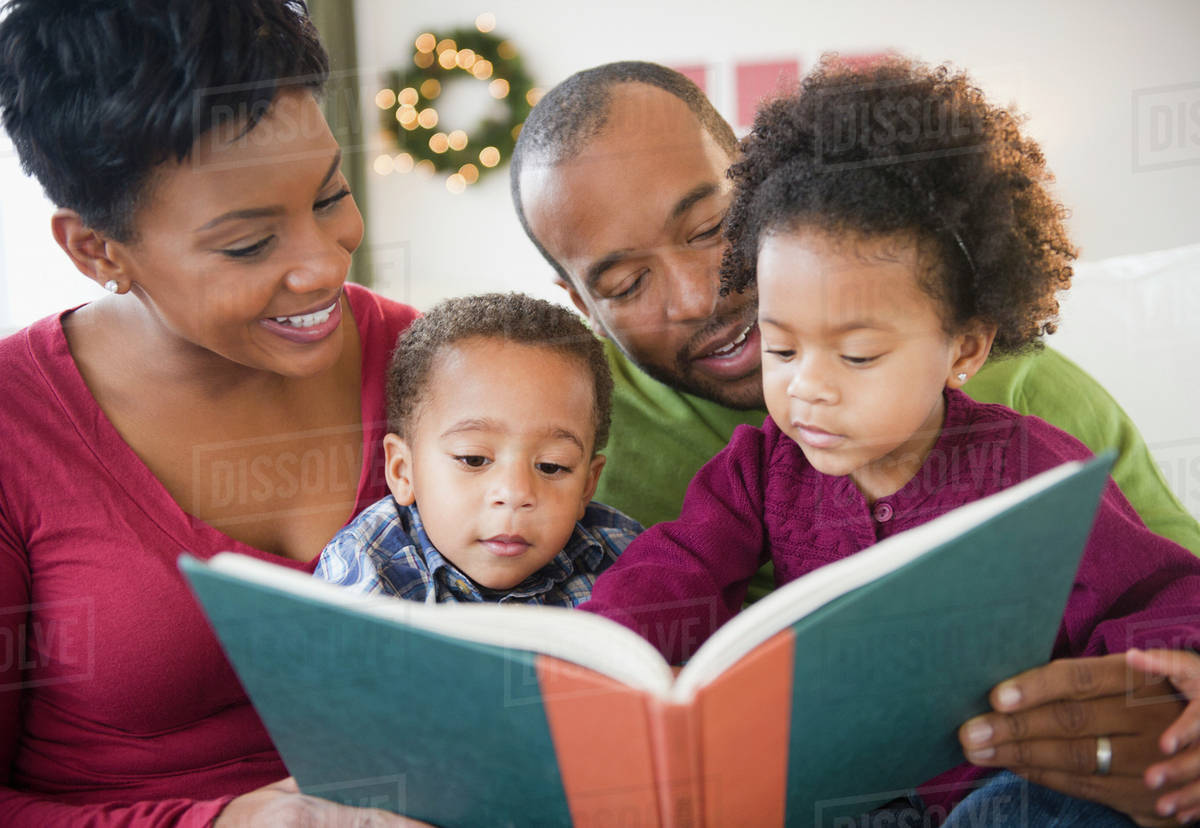 black family reading book together stock photo dissolve