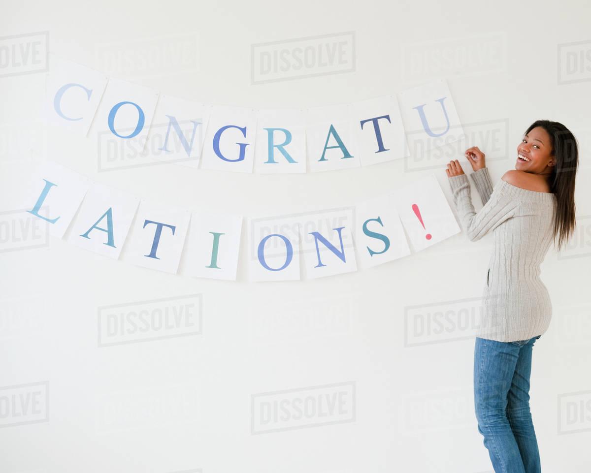 mixed race woman putting up congratulations sign stock photo