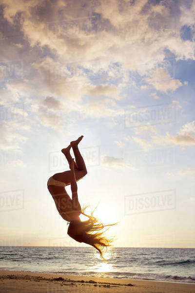 Silhouette of mixed race woman doing backflip on beach Royalty-free stock photo