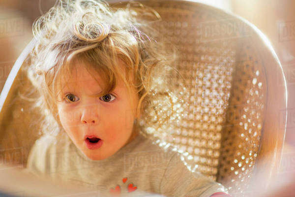 Caucasian baby boy gasping in wicker chair Royalty-free stock photo