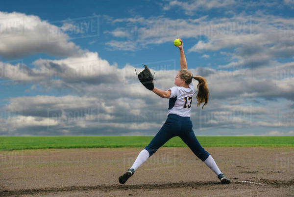 Caucasian softball player pitching ball in field Royalty-free stock photo