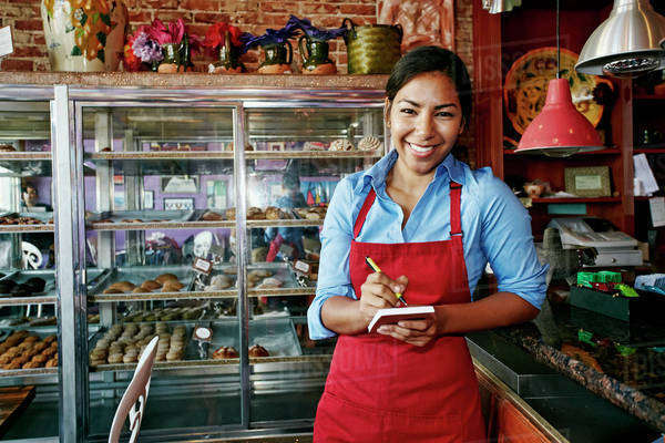 Hispanic waitress taking orders in bakery Royalty-free stock photo