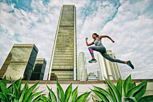 African American woman leaping on urban rooftop Royalty-free stock photo