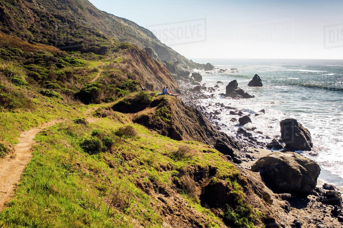 People sitting on rocky coastline trail near ocean Royalty-free stock photo