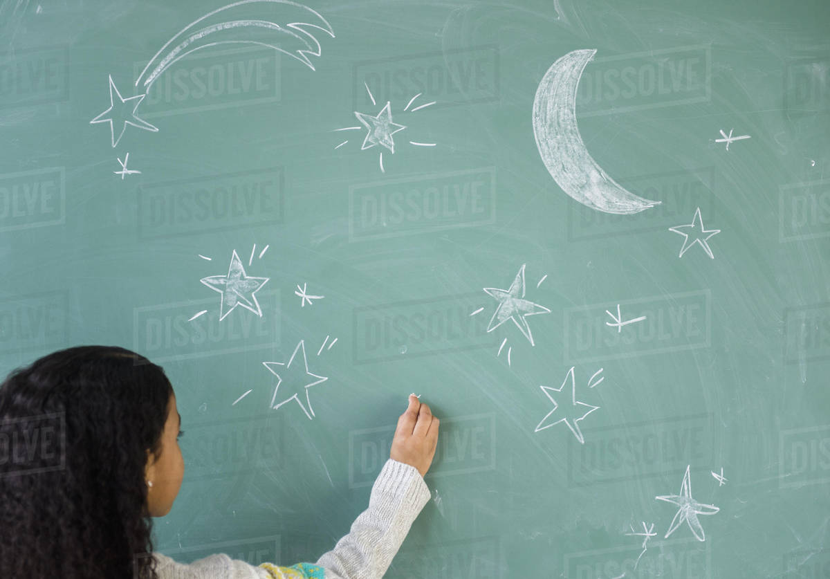 Mixed race student drawing stars on chalkboard in classroom Royalty-free stock photo