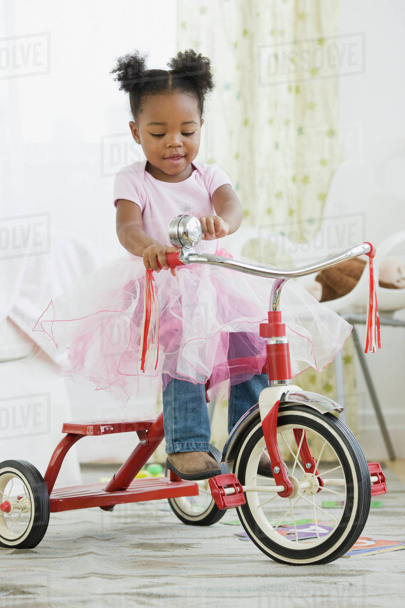African American girl in costume riding tricycle Royalty-free stock photo