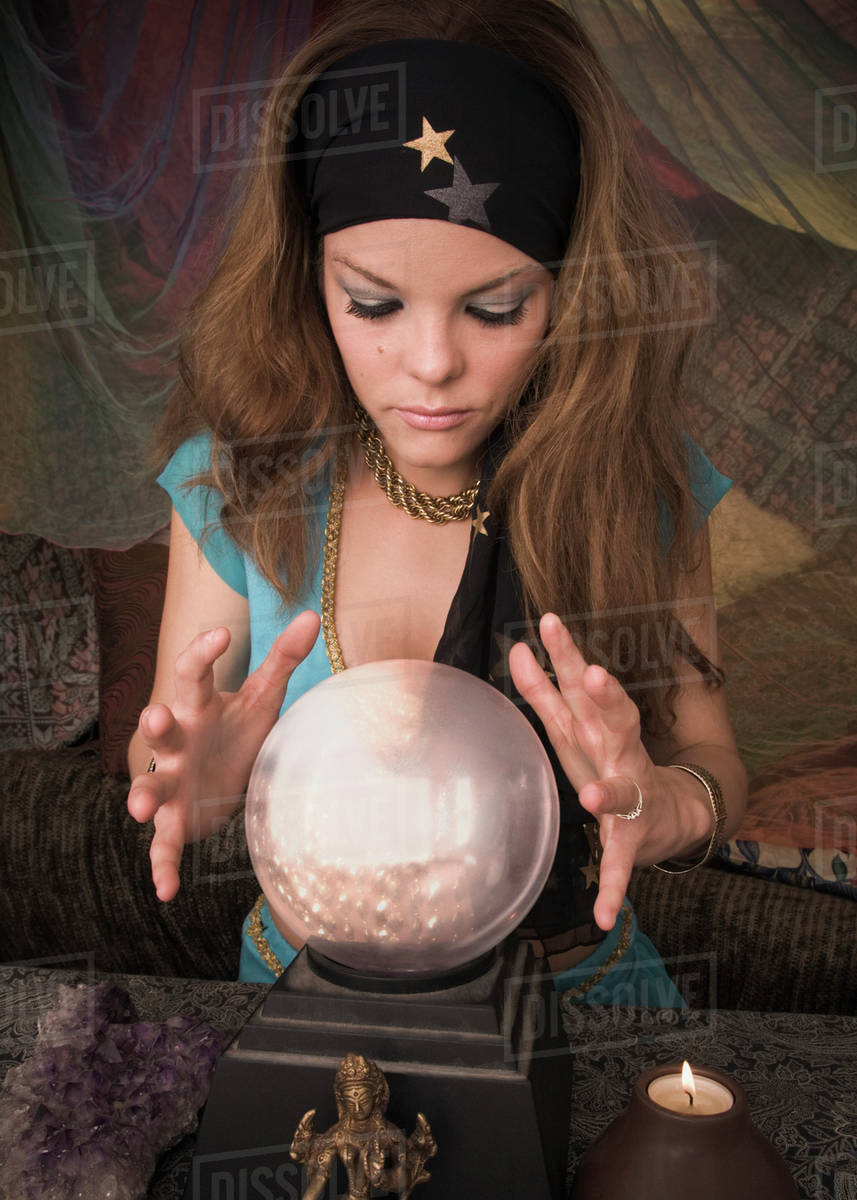 Woman dressed at fortune teller looking into crystal ball stock photo