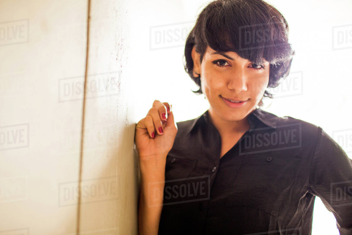 Smiling Hispanic woman leaning on wall Royalty-free stock photo