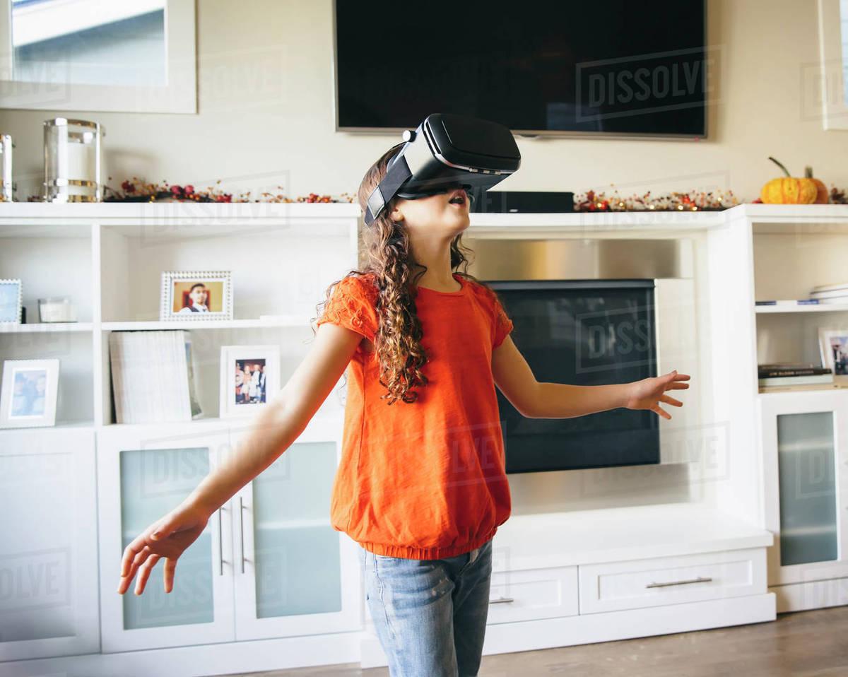 Mixed race girl using virtual reality goggles Royalty-free stock photo