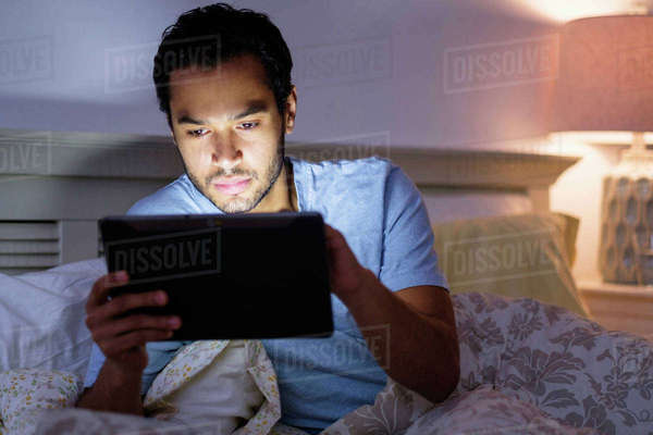 Hispanic man using digital tablet in bed Royalty-free stock photo