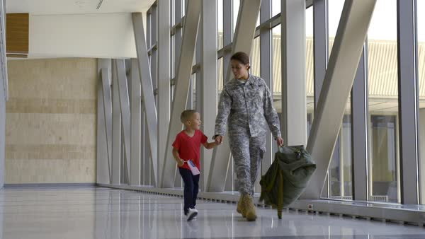 African American soldier and son walking in airport Royalty-free stock video