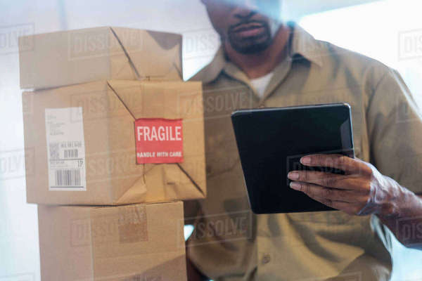 Black delivery man using digital tablet Royalty-free stock photo