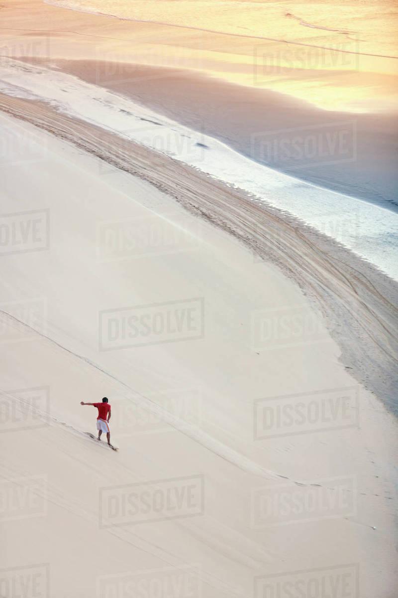 Man Surfing On Sand Dunes On Beach Stock Photo
