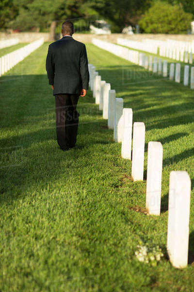 Black man leaving bouquet at gravestone at military cemetery Royalty-free stock photo