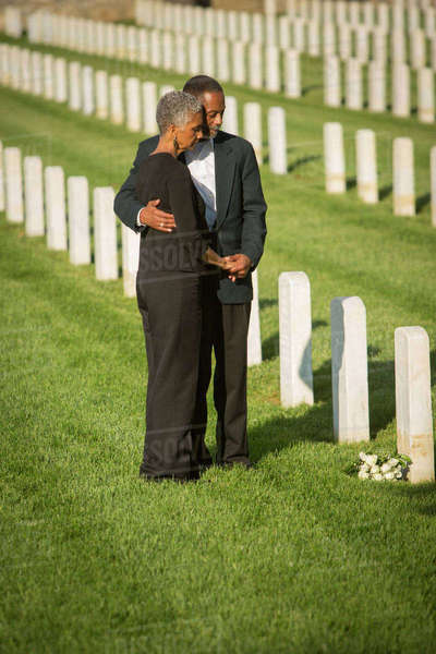Black couple hugging in military cemetery Royalty-free stock photo