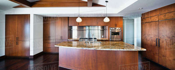 Kitchen having brown cabinets and island at home Royalty-free stock photo
