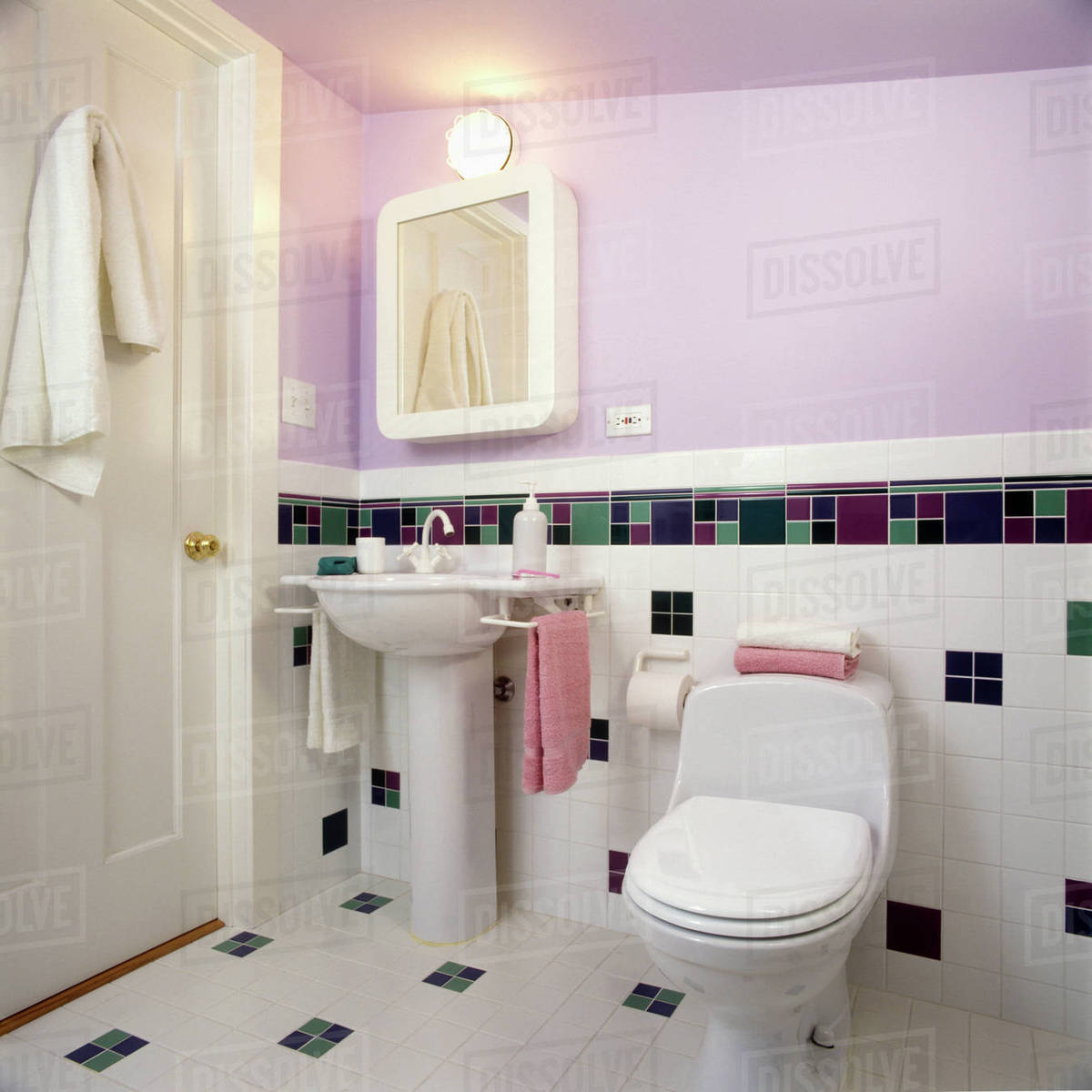 Contemporary bath in lavender and white with pedestal sink, partial tiled wall with checkered pattern in green, violet and purple, wall mounted medicine ...