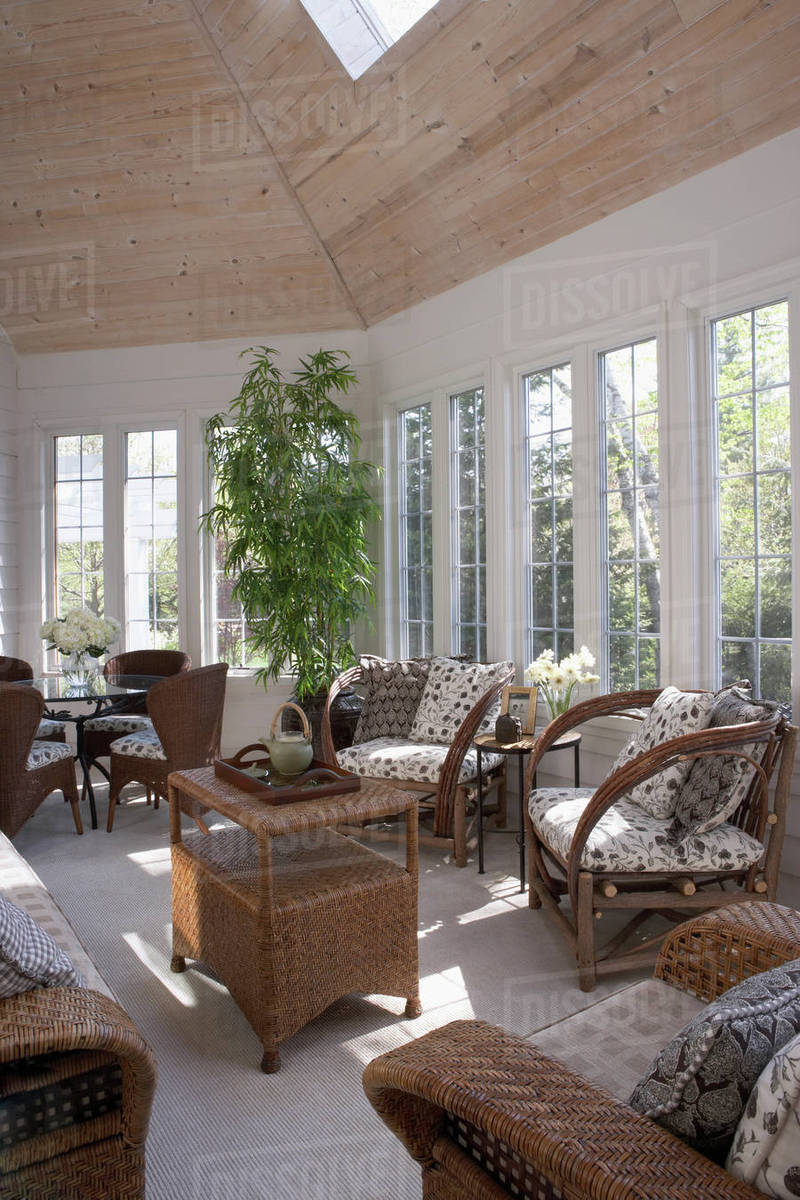 Sunroom With Brown Wicker Furniture, Skylight, Pattern Cushions, Windows,  Beige Carpet, Wood Paneled Ceiling, Tray With Teapot, Game Table With Four  Chairs, ...