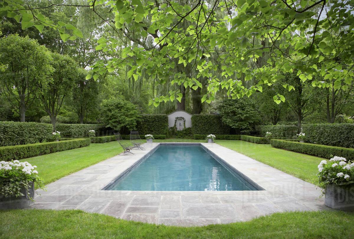 Formal shaped hedge garden with narrow pool , bluestone patio, white ...