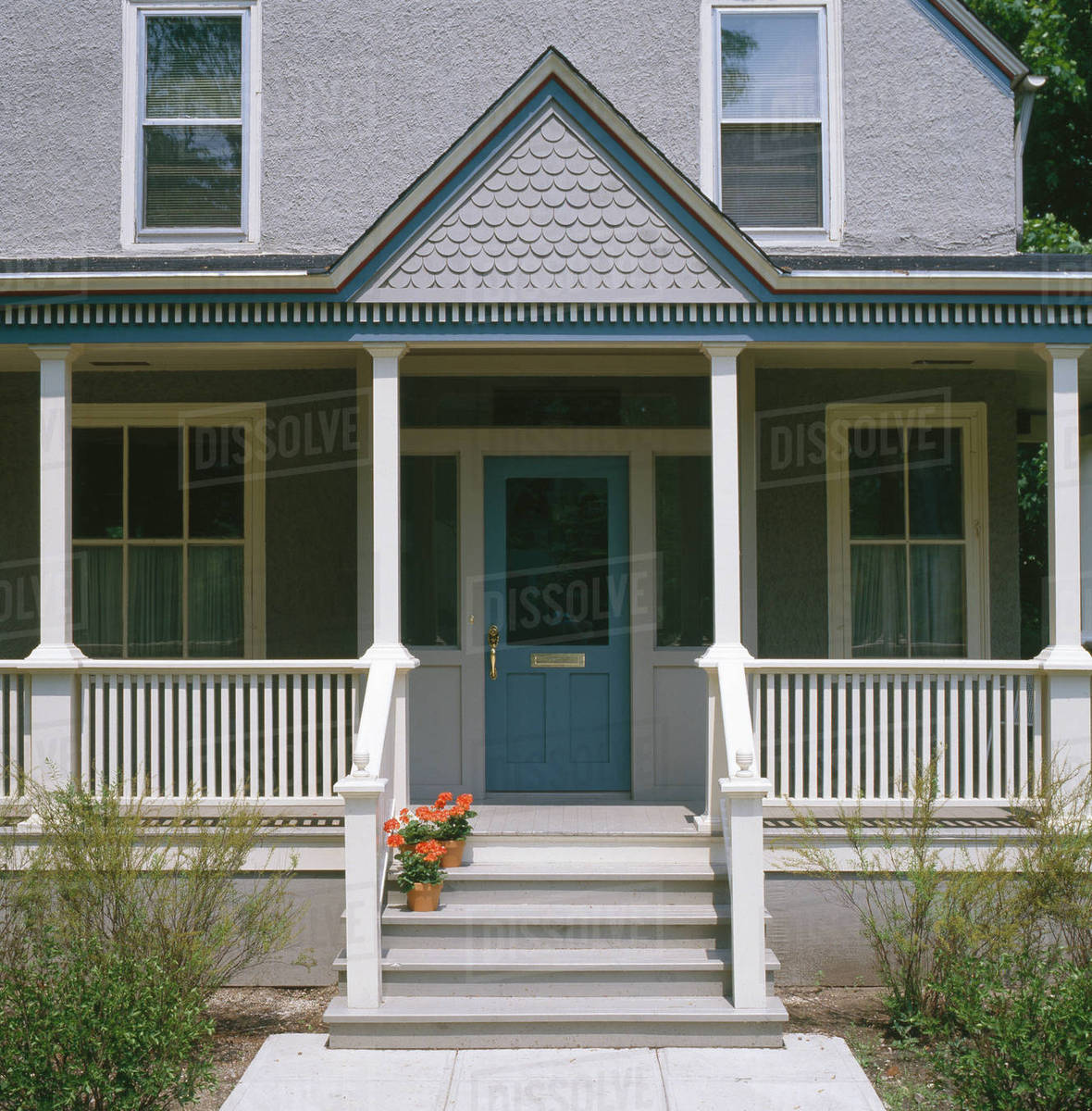 Front Porch Of Gray Stucco House With Dark Blue Trim