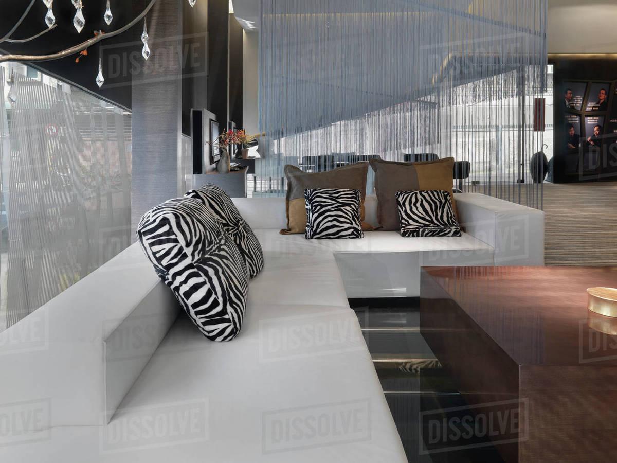 Large modern sectional sofa with animal print throw pillows - Stock ...