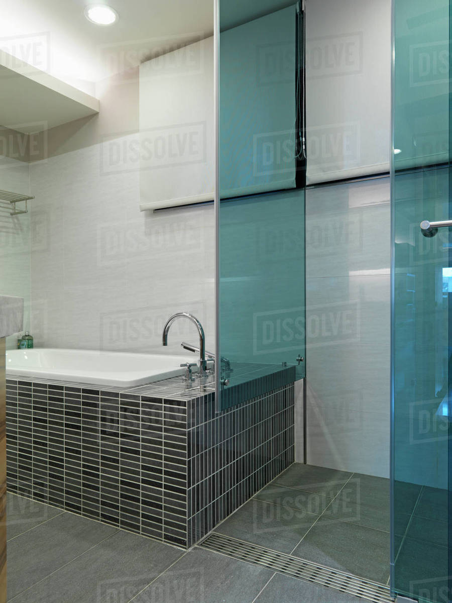 Mosaic tile bathtub and glass shower - Stock Photo - Dissolve