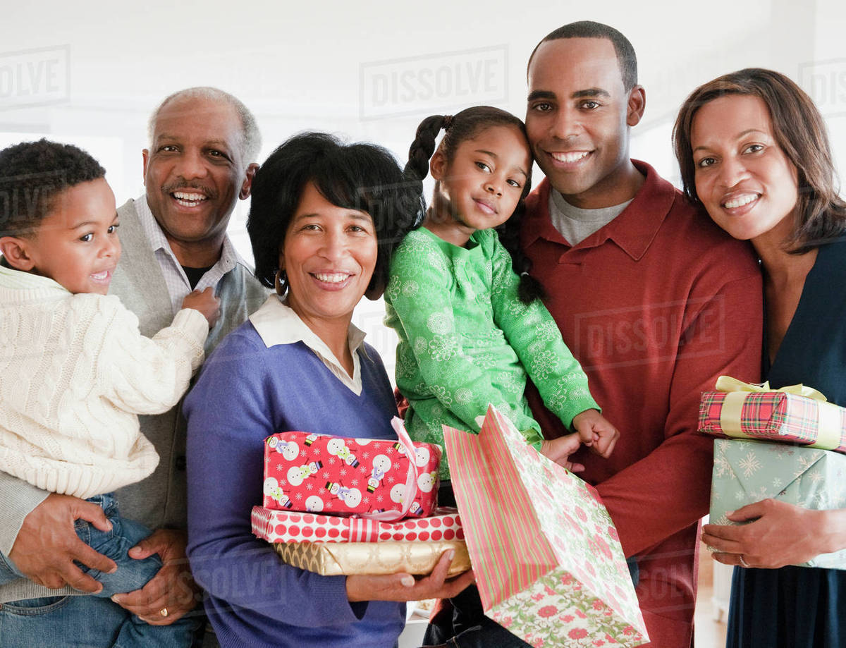 African American family holding Christmas gifts - Stock Photo - Dissolve